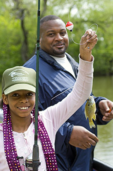 A young girl learns to fish for panfish at Palmer Park in Detroit.