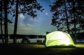 yellow tent, lit up from within, on the shores of Big Bear Lake, dark sky with hundreds of stars