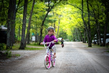 Bundled-up little girl, smiling, riding her bike down a gravel trail, bright green trees in background