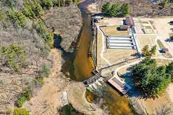 An aerial image shows the Lower Manistee River weir and ponds.