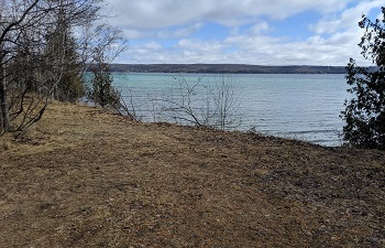 view from the shore of a 2-plus-acre land parcel on Torch Lake with 200 feet of lake frontage, blue sky and clouds