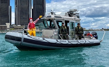 Ronald McDonald, waving, and DNR conservation officers, all wearing life jackets while on a patrol boat on the water