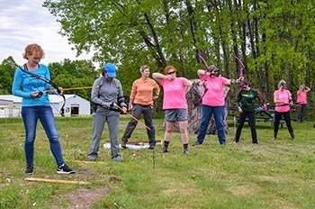 A group of women is shown outdoors shooting arrows at a BOW archery event in Marquette County.