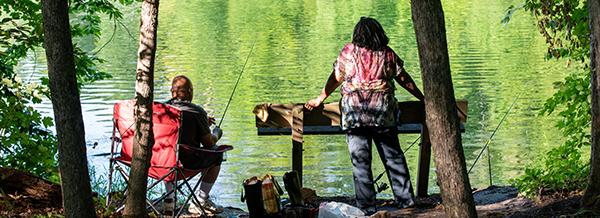man with fishing rod and woman on wooded river bank