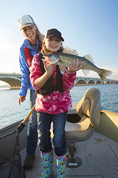 Smiling girl holding walleye and her mom in boat