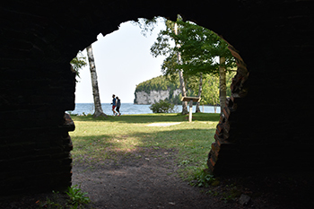 Two people walking with harbor and cliffs in background, seen through brick archway