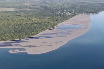 An aerial view shows Lake Superior and its shoreline covered in stamp sands in Keweenaw County.