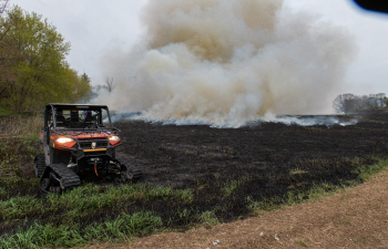 prescribed burn on field with fire equipment