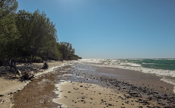 long view of the sandy, rocky beach, blue sky and shoreline waves at Muskellonge State Park in Luce County