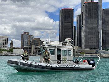 conservation officers on boat against backdrop of Detroit