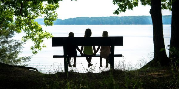 Three kids on a bench hold hands, facing a lake, framed by leafy trees