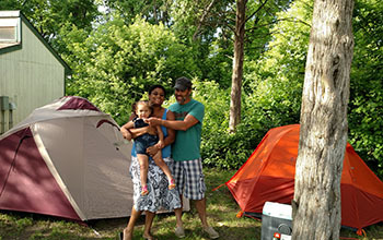 parents holding baby in front of tent and camper cabin