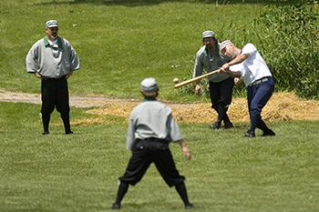 four men playing in vintage baseball game