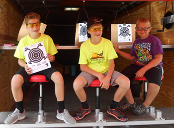Three boys in shooting sports trailer with targets