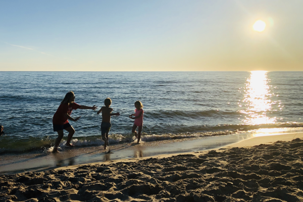 An adult and two children running in the water at Muskegon State Park beach