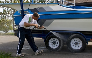 a man uses a spray hose to clean off the tires on his boat trailer