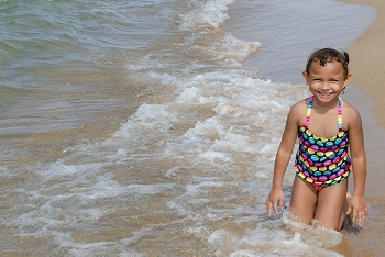 little girl with dark, curly hair, in a multicolored bathing suit, smiles at the camera while kneeling in the shallow beach surf
