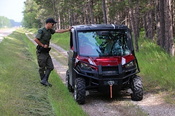 a male DNR conservation officer talks with the operator of a red off-road vehicle, facing the camera, on a two-track dirt trail