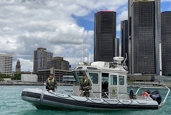 conservation officers aboard a DNR patrol boat on the Detroit River, city skyline and buildings in background