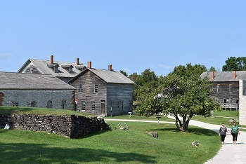 a few people walking on the sidewalk in between the historic buildings at Fayette Historic State Park