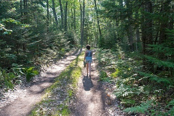 view of a girl wearing shorts and tank top, carrying shoes, walking away from the camera down a forested, sunlit trail