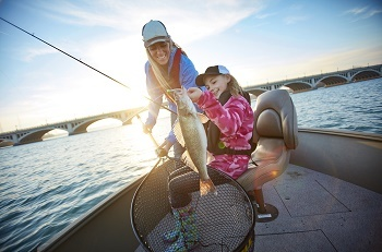 Smiling woman, long blonde hair, baseball cap, helps a young girl hold up the fish she just caught, on a boat in river