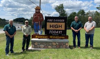 A digital sign featuring Smokey Bear and an electronic screen stating the day's fire danger as