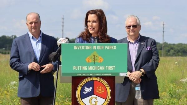 Gov. Gretchen Whitmer stands at a podium with Genesee County officials to announce the new state park