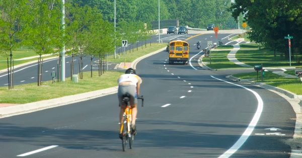A cyclist and school bus are seen on a tree-lined road in Kalamazoo