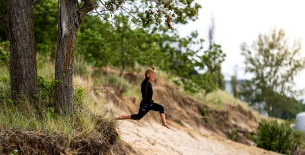 A young boy leaps beyond the forest edge onto a sandy beach, arms in the air