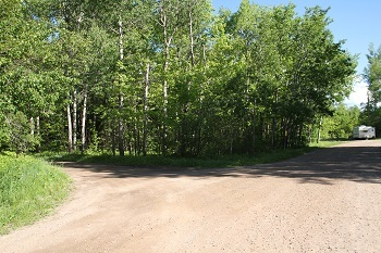 view of a partially forested area, with a wide gravel clearing, and a camper parked in the back on the right
