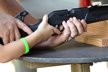 The hands of a volunteer and a child are shown on an air rifle at the DNR Pocket Park in Delta County.