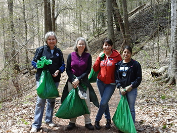 volunteers in forest holding trash bags