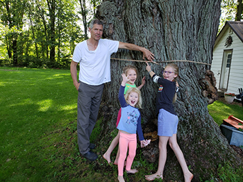 man and three young girls measuring base of large tree