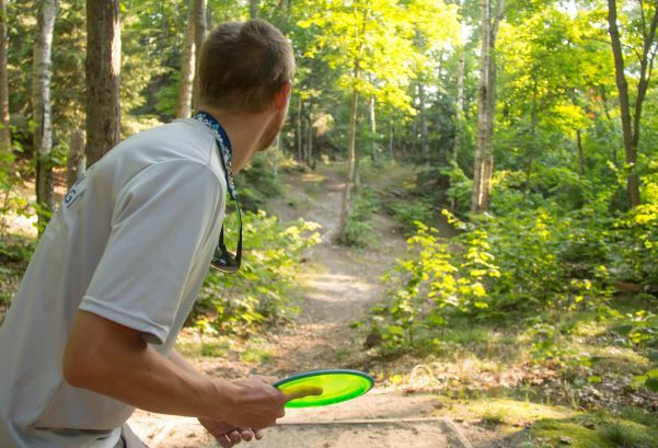 A man leans forward, preparing to throw a bright green disc into the forest in a game of disc golf