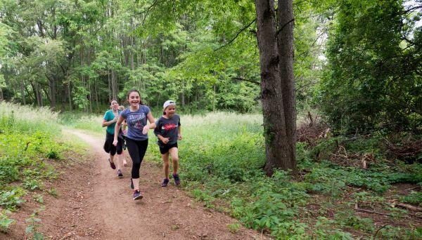A group of children run on a dirt path through a green forest