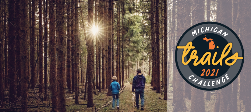 father, child and dog walking on trail with filtered sunlight, Michigan Trails Week logo