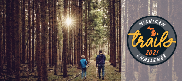 A parent and child hike on a forest trail; a Michigan 2021 Trails Week Challenge graphic is shown