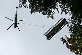 A helicopter flies overhead carrying a segment to the pedestrian bridge.