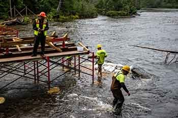 Workers get ready to place the pedestrian bridge on temporary abutments.