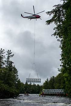 A wide shot shows a helicopter placing a bridge segment into place.