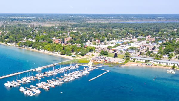 Aerial view of a coastal town, East Tawas, and harbor, with blue water and lots of trees
