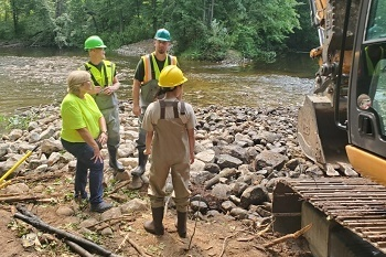 a small group of men and women in work gear and hard hats stand on a rocky riverbank, next to heavy equipment