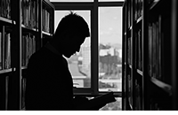 Photo of student reading book in library