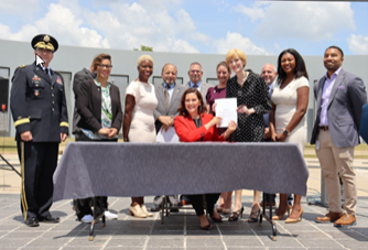 Photo of Governor Whitmer signing bill with other people looking on