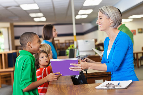 Librarian handing books to students