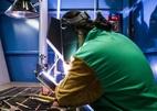 A welder welding in a welding booth.