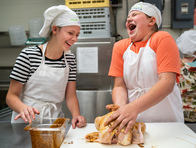 Two students in a culinary arts summer camp seasoning a whole chicken.