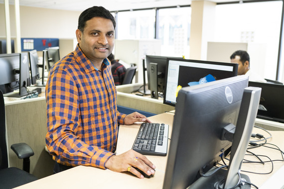 Ram Kumar Kantamneni standing at his computer at his desk.