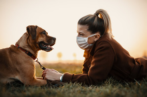Dog with owner. Owner wearing a mask.